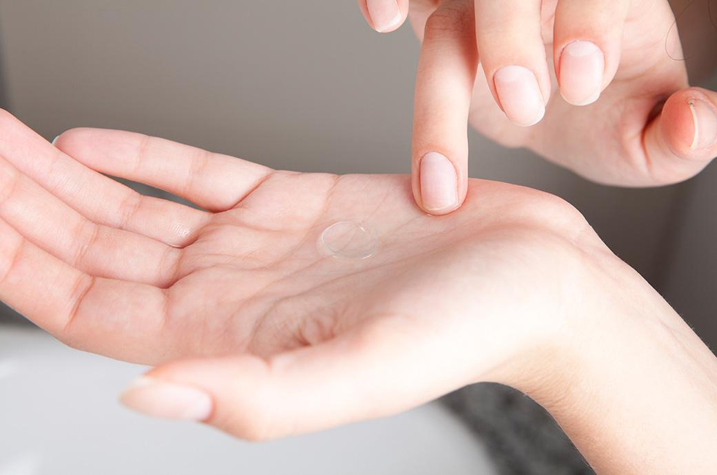 Las manos de alguien con un lente de contacto en su palma