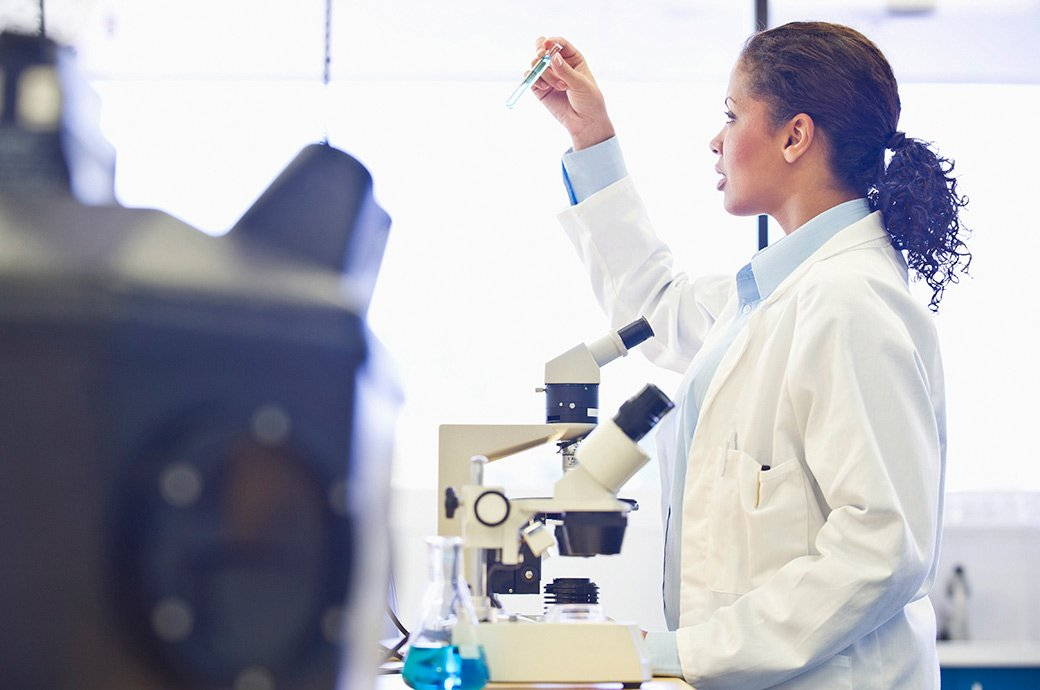 Doctor mirando en el microscopio en el laboratorio.