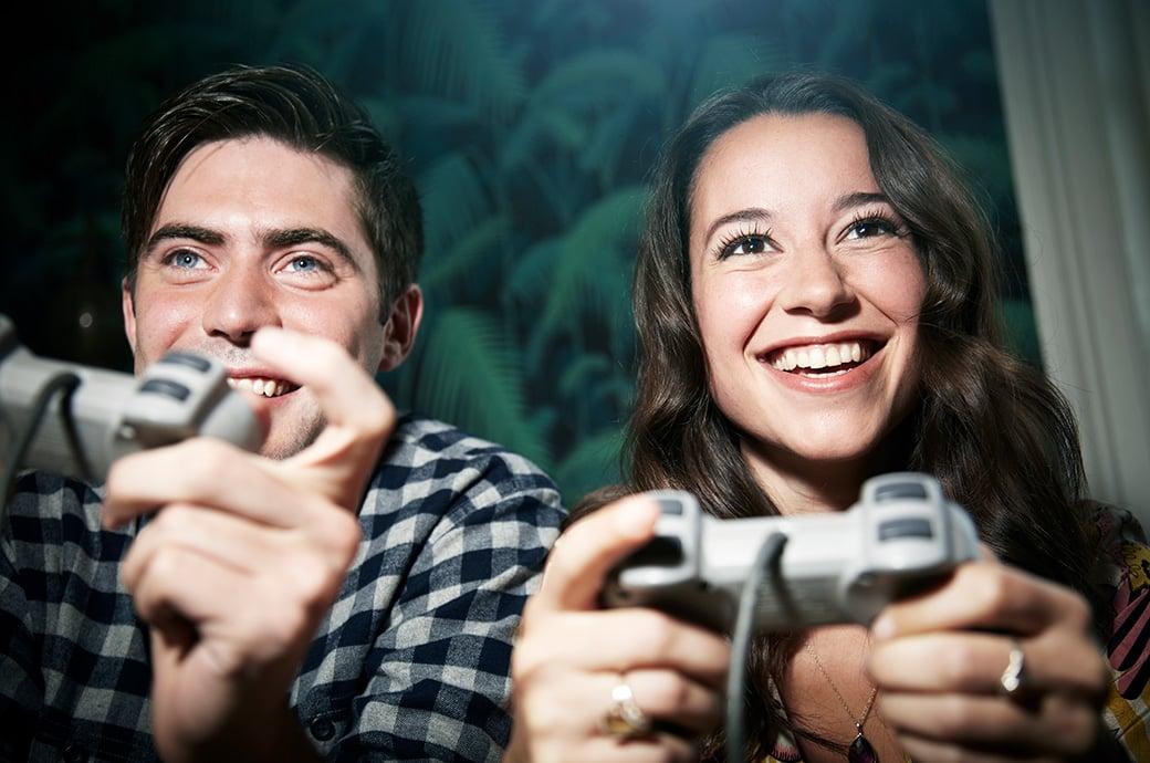 Dos adultos con controladores jugando videojuegos
