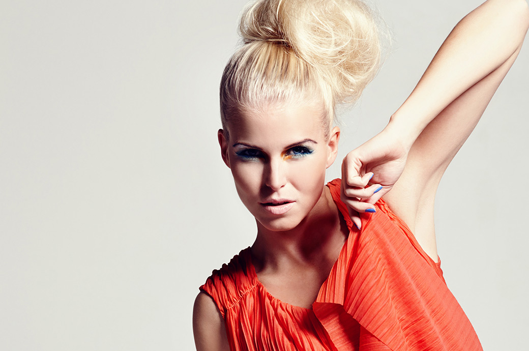 Una mujer joven y de moda posa con el codo hacia arriba mirando a la cámara