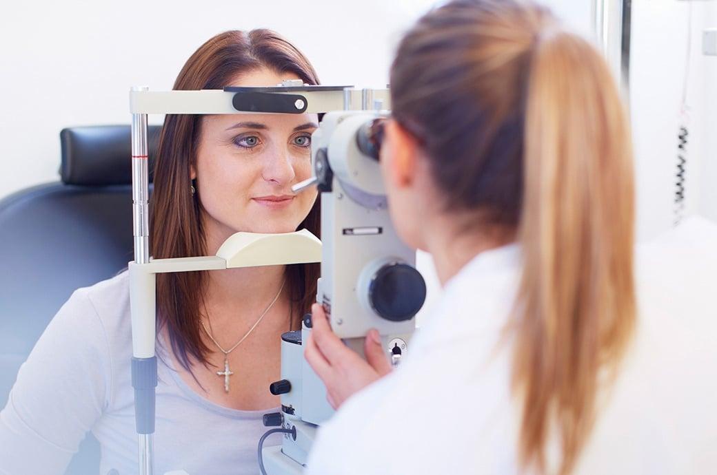 La cámara se enfoca en una mujer joven que mira a través de una cámara de retina mientras su doctor mira por el otro lado
