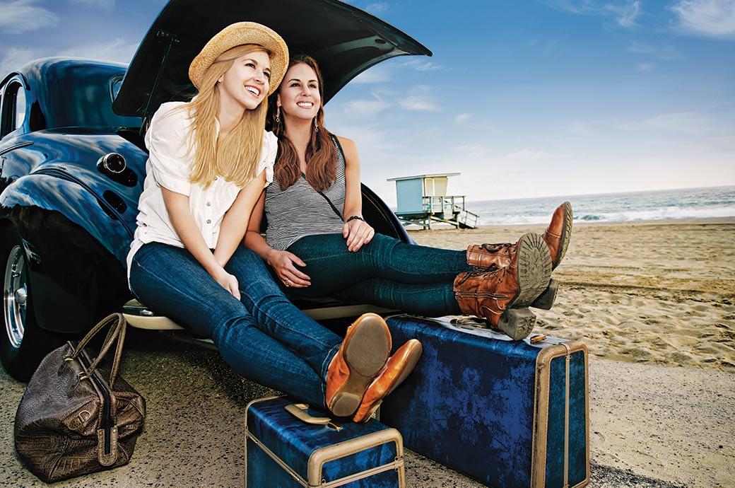 Dos muchachas que se sientan en la cajuela de un coche cerca de la playa con su equipaje listas para viajar