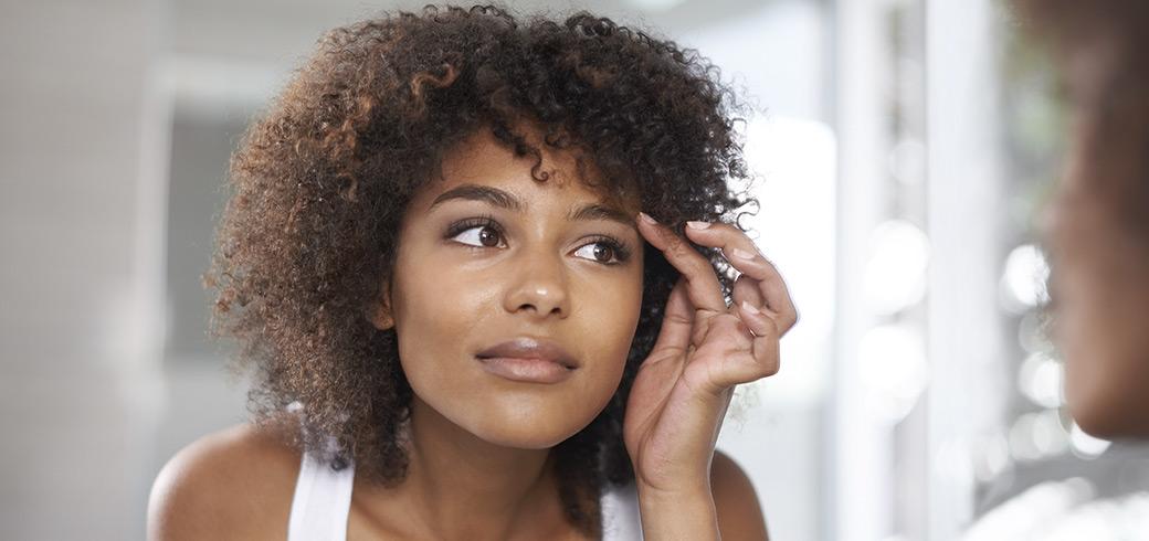 Una mujer joven que mira sus ojos en el espejo